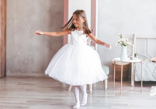 Uma menina em um lindo vestido branco dança em uma sala iluminada. está girando com a música. infância feliz