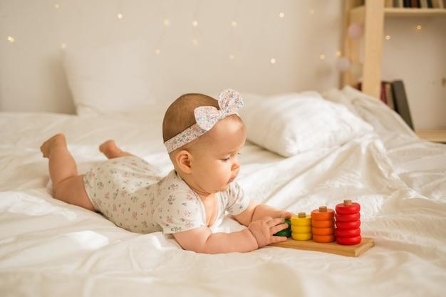 Uma menina em um macacão colorido e bandana brinca com um brinquedo educacional em um cobertor branco na cama. desenvolvimento anterior