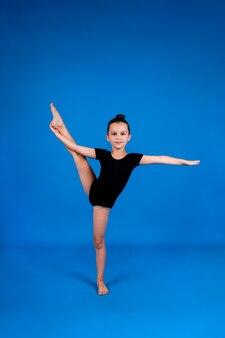 Uma menina em um maiô preto realiza exercícios de alongamento em um fundo azul com um lugar para o texto