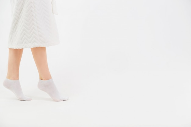 Uma menina em um roupão branco e meias vai em meias depois de um banho. close-up das belas pernas delgadas femininas. vista lateral.