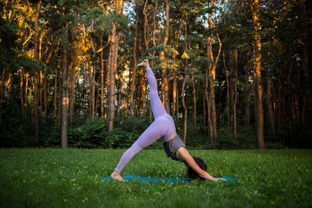 Uma menina em um uniforme de esportes executa uma pose de ioga invertida na natureza ao pôr do sol