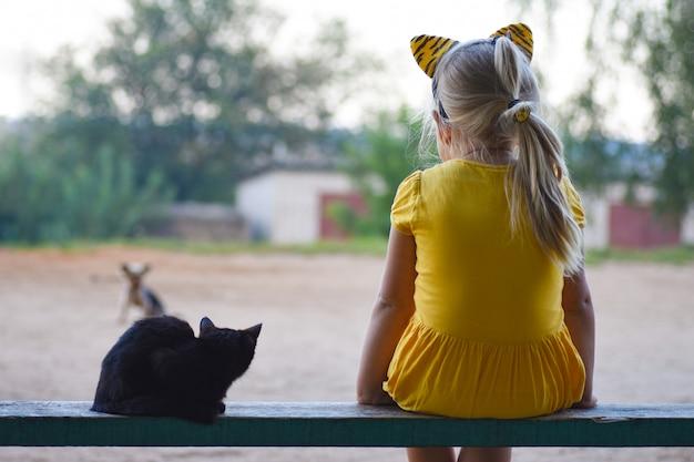 Uma menina em um vestido amarelo com um pequeno gato preto está sentado em um banco e olhando para um cachorro, vista traseira
