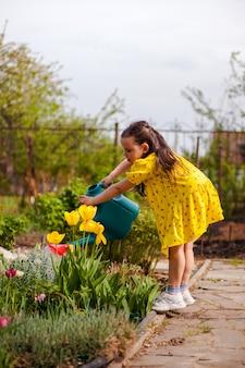 Uma menina em um vestido amarelo se curva para as flores amarelas para regar de um jardim azul regando c ...