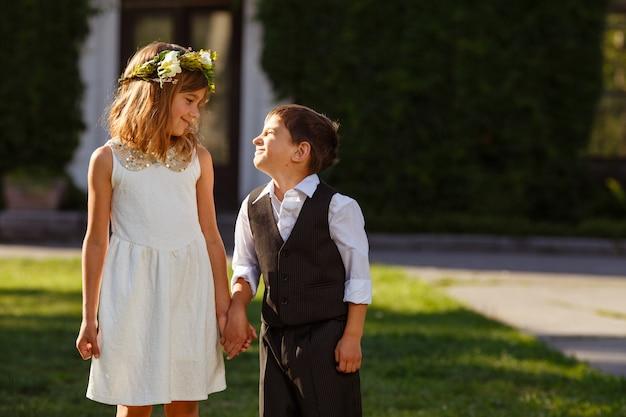 Uma menina em um vestido branco segura a mão de um menino em um terno elegante