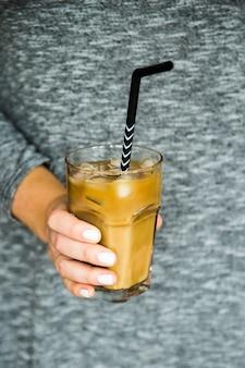 Uma menina em um vestido cinza com uma mão segura um copo grande de café gelado com leite e um canudo preto. conceito de bebida de resfriamento de verão
