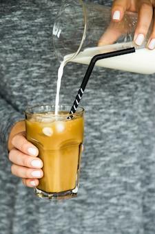 Uma menina em um vestido cinza derrama leite em um copo grande com café gelado e um canudo preto. conceito de bebida de resfriamento de verão