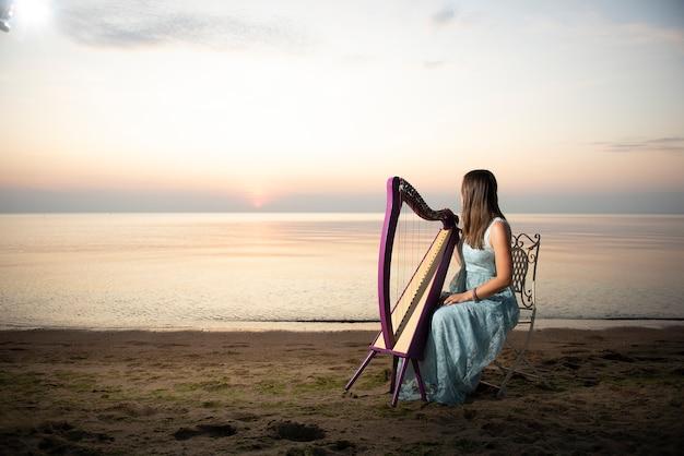 Uma menina em um vestido de flor toca uma harpa celta à beira-mar ao pôr do sol