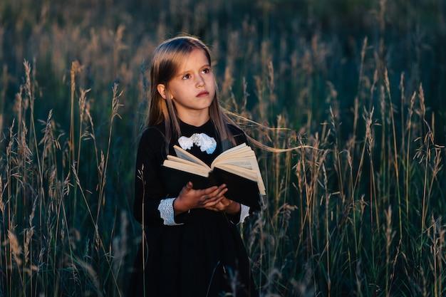 Uma menina em um vestido preto fica na grama alta e segura um livro verde à luz do sol poente. uma criança com uma expressão facial pensativa.