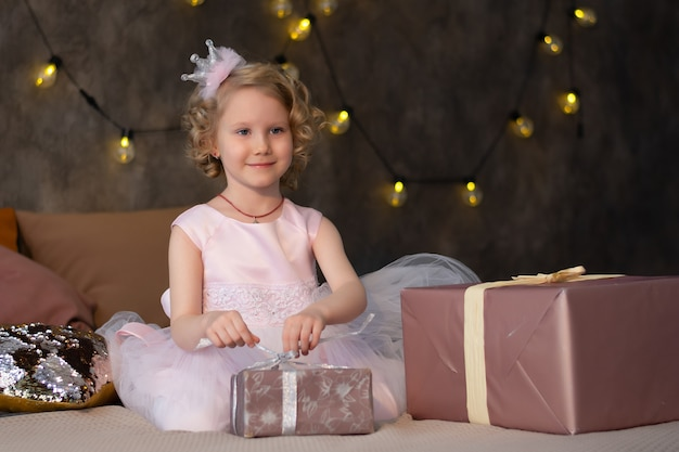 Uma menina em um vestido rosa e uma coroa na cama com presentes.