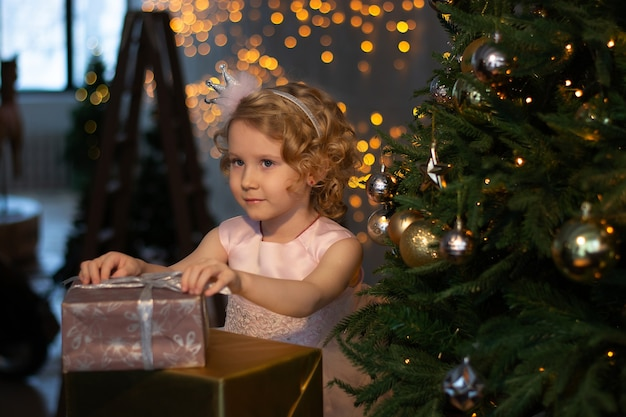 Uma menina em um vestido rosa e uma coroa perto da árvore de natal com presentes.