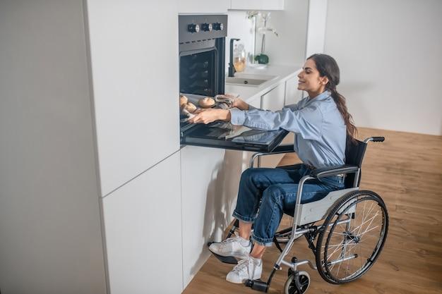 Uma menina em uma cadeira de rodas abrindo o forno na cozinha enquanto cozinha algo