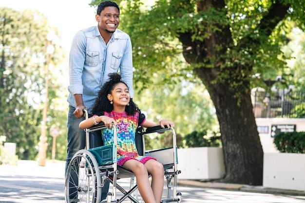 Uma menina em uma cadeira de rodas curtindo e se divertindo com o pai durante uma caminhada ao ar livre