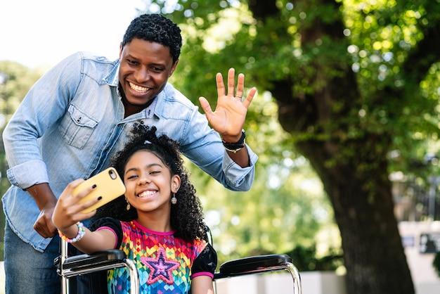 Uma menina em uma cadeira de rodas, curtindo e se divertindo com o pai, enquanto tirava uma selfie com o celular ao ar livre na rua.