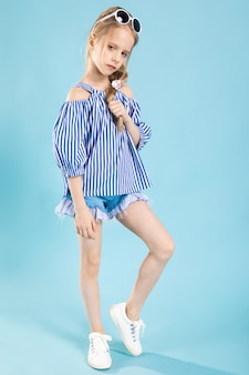 Uma menina em uma camiseta e shorts com óculos na cabeça está de pé em um azul