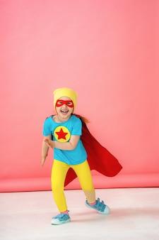 Uma menina em uma fantasia de super-herói, correndo para a frente em um rosa