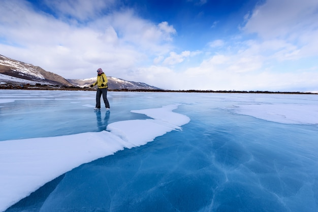 Uma menina em uma jaqueta amarela e patins de gelo fica no lago azul do lago baikal
