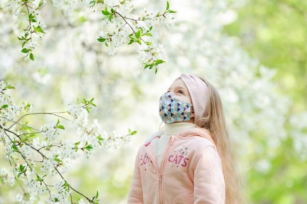 Uma menina em uma máscara médica olha para uma flor de árvore.