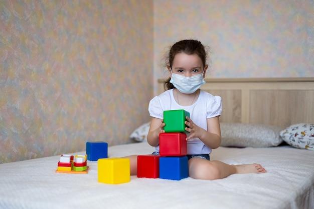 Uma menina em uma máscara protetora brinca com brinquedos educativos