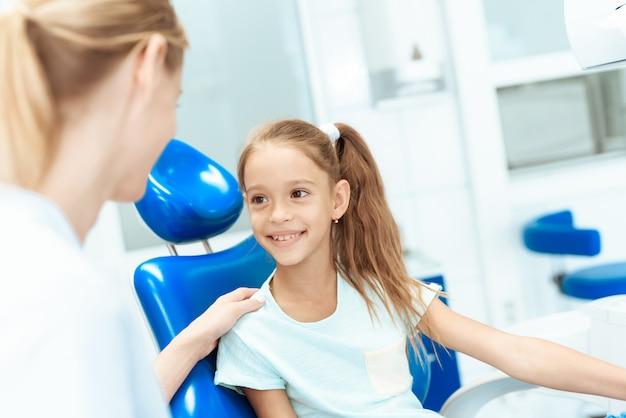 Uma menina em uma recepção com um dentista.