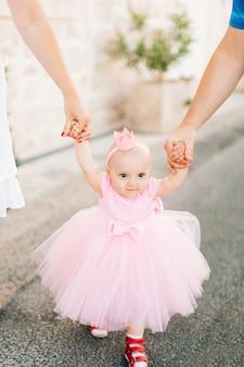 Uma menina encantadora com um tênis vestido rosa e uma coroa na cabeça