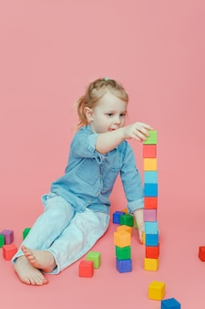 Uma menina encantadora constrói uma torre de cubos coloridos de madeira.