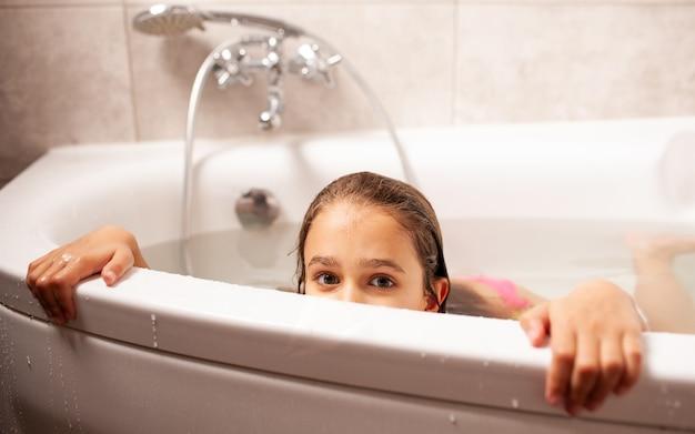 Uma menina engraçada com óculos de natação retrata um monstro marinho tomando banho