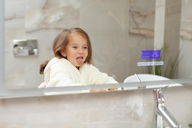 Uma menina engraçada e maluca em um roupão de banho se entrega na frente do espelho no banheiro e faz uma careta