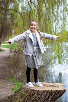 Uma menina engraçada em uma caminhada na floresta do início da primavera gosta da natureza.
