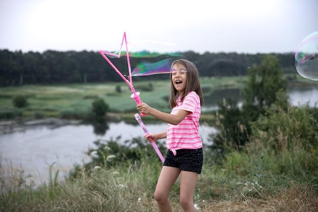 Uma menina engraçada sopra bolhas de sabão no verão em um campo, atividades de verão ao ar livre.
