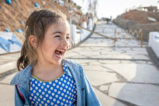 Uma menina engraçada viu algo interessante à distância e rindo.