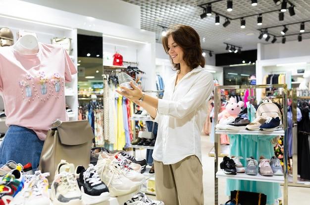 Uma menina escolhe lindos sapatos esportivos na loja