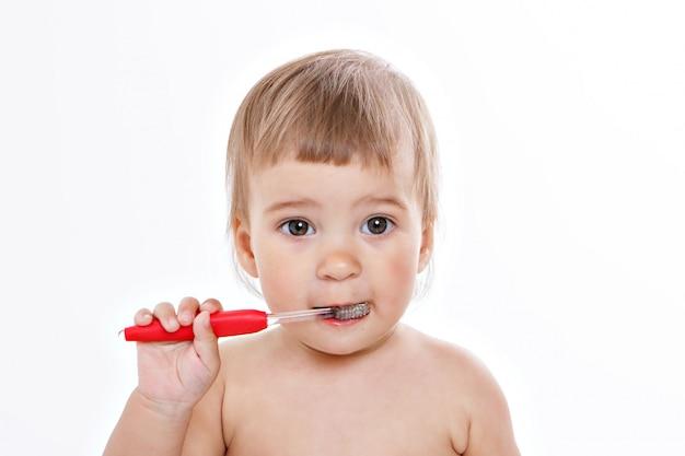 Uma menina escova os dentes em um branco. retrato de uma criança com uma escova de dentes vermelha.