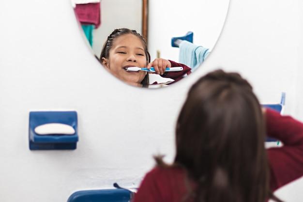 Uma menina escovando os dentes na frente de um espelho em um banheiro