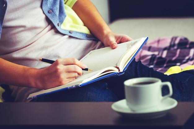 Uma menina escreve em um caderno, sentado em um sofá