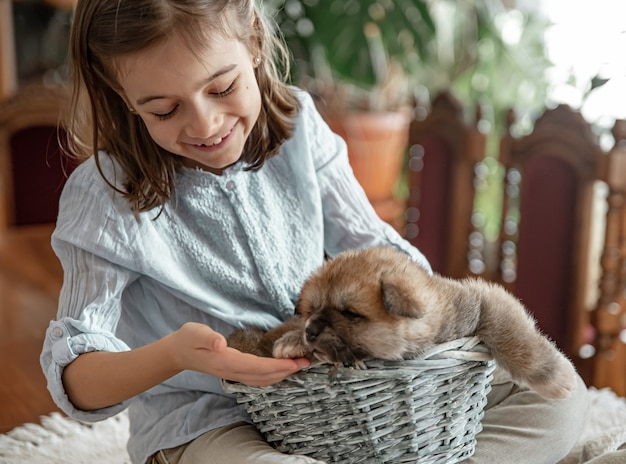 Uma menina está brincando com seu cachorrinho fofo