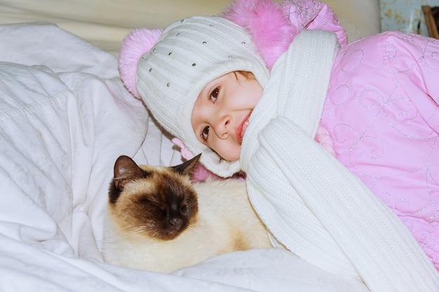 Uma menina está brincando com um gatinho uma menina brinca com um gato