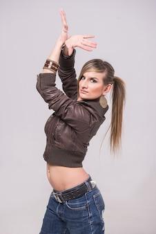 Uma menina está de pé em uma jaqueta marrom e posando.