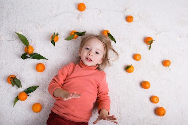 Uma menina está deitada no chão claro, um monte de tangerinas estão espalhadas ao seu redor.