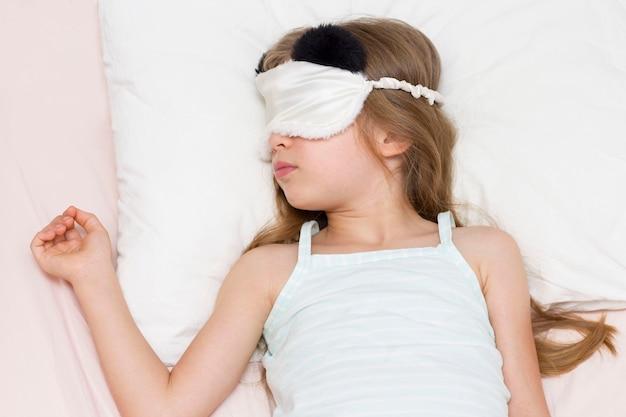 Uma menina está dormindo na cama, debaixo de um cobertor branco, com uma máscara para dormir com um urso.