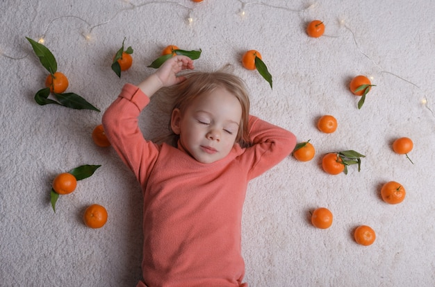 Uma menina está dormindo no chão claro, com um monte de tangerinas espalhadas ao seu redor.