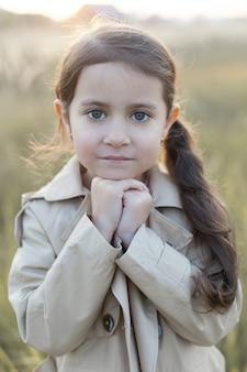 Uma menina está em um campo. mãos cruzadas conceito de paz, esperança, sonhos,