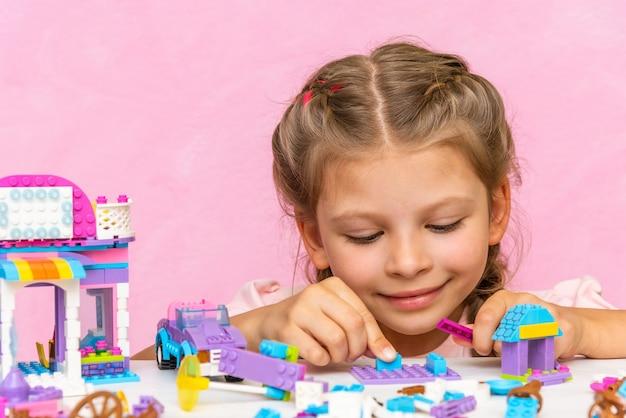 Uma menina está jogando um kit de construção em uma mesa-de-rosa.