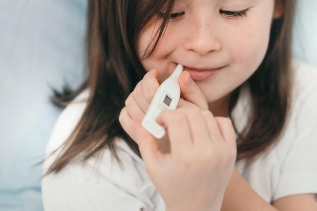 Uma menina está medindo sua temperatura. a criança está resfriada e está sendo tratada em casa. repouso na cama para resfriados. resfriados sazonais em crianças