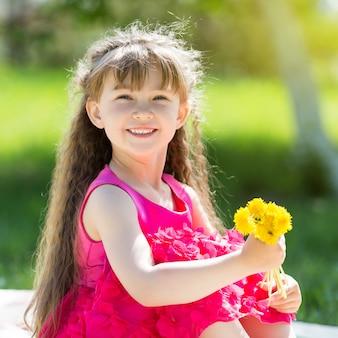 Uma menina está segurando um buquê de flores.