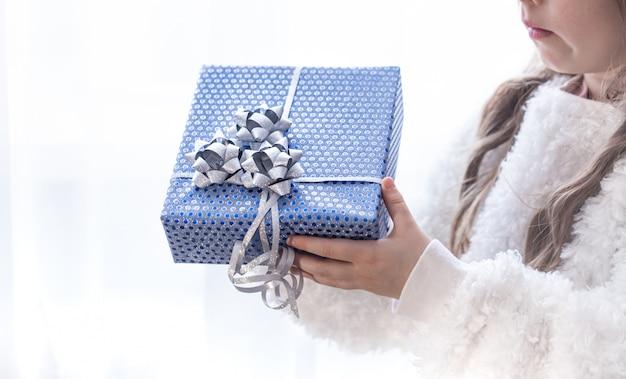 Uma menina está segurando um presente de natal azul.