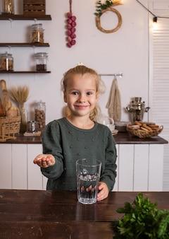 Uma menina está sentada à mesa da cozinha com um copo d'água e bebendo vitaminas