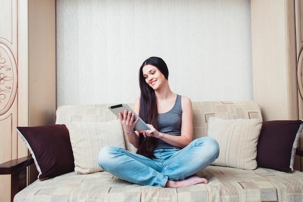 Uma menina está sentada com um tablet em um sofá bege