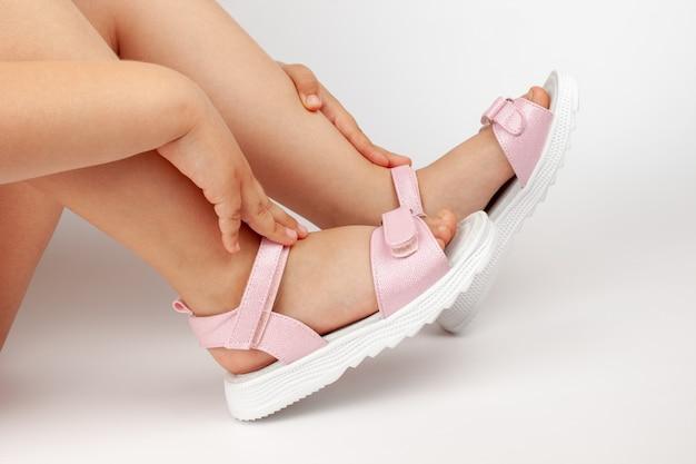 Uma menina está sentada em um fundo branco em sandálias infantis rosa brilhantes