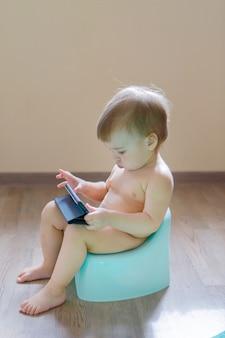Uma menina está sentada em um penico e brincando com o telefone dela. vendo desenhos animados. aprendendo a trabalhar com gadgets. conceitualidade com a tecnologia moderna, digestão saudável, housebreaking