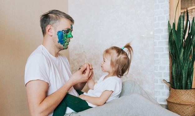 Uma menina está sentada no colo do pai, pintando seu rosto com um pincel de tinta a óleo. arte corporal